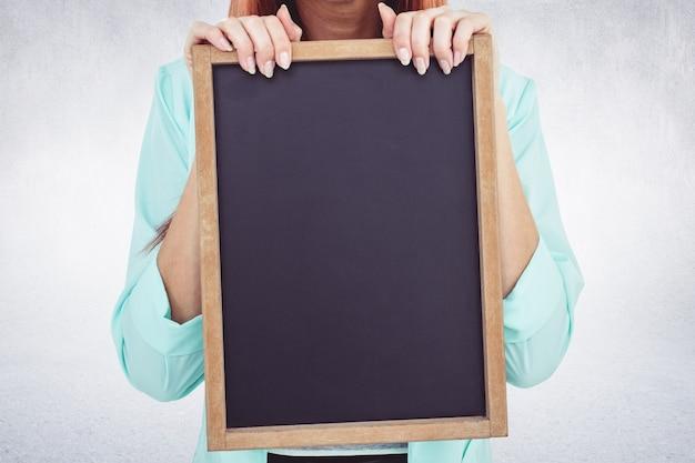 Close-up das mãos segurando um pequeno quadro-negro