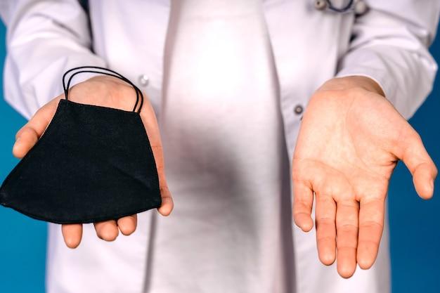 Close-up das mãos segurando uma máscara facial preta artesanal, isolada na parede azul. conceito de deficiência de máscaras médicas.