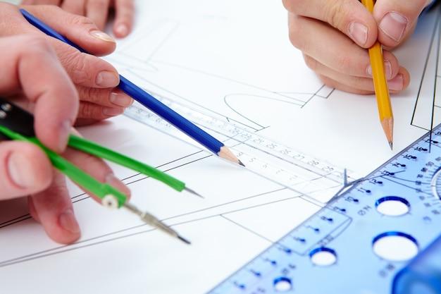 Close-up das mãos trabalhando com lápis e réguas