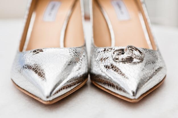 Close-up das noivas sapatos de prata dedos e alianças de casamento no chão de mármore, foco seletivo
