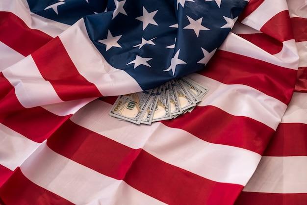 Close up das notas de dólar americano na bandeira nacional