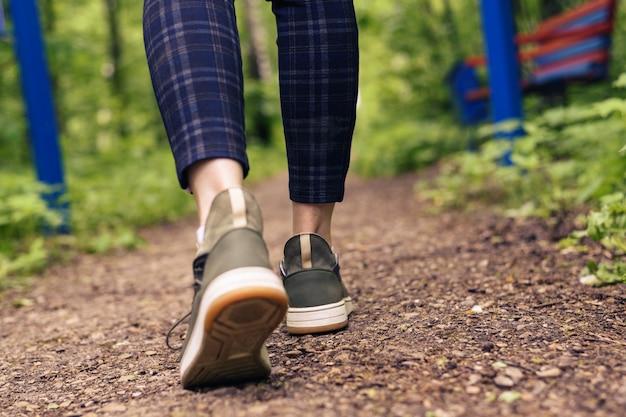 Close-up das pernas das mulheres de tênis verdes e calças em uma gaiola ir em uma estrada da floresta. hls, ande ao ar livre