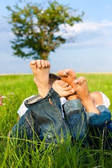 Close-up das pernas de duas pessoas, deitado em um prado