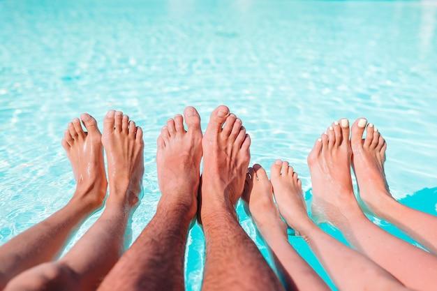 Close up das pernas de quatro pessoas ao lado da piscina