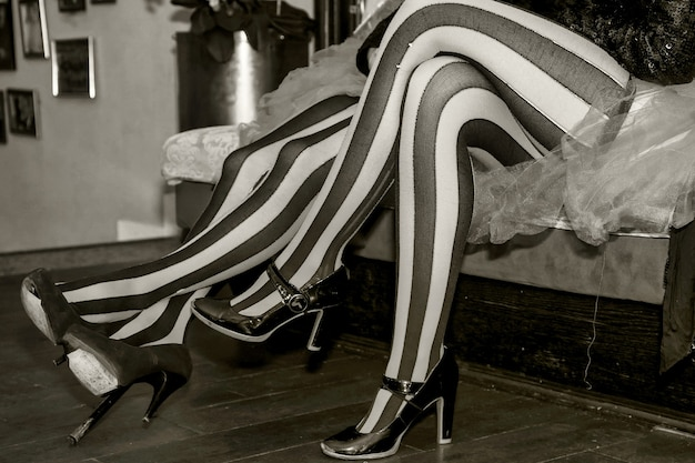Close-up das pernas de um artista de circo de terno e meias listradas de preto e vermelho no camarim. artista de circo à espera de um convite para entrar no palco ou arena. performance de concerto para fundos