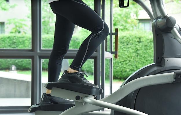 Close-up das pernas de um jovem esportista masculino usando um aparelho elíptico em uma academia