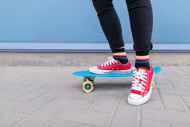 Close-up das pernas de uma garota de tênis vermelho em pé em um skate azul em uma parede azul