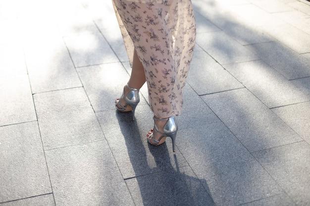 Close-up das pernas de uma mulher de salto alto em sapatos prateados descalços, andando pela rua de asfalto. dia mundial do turismo