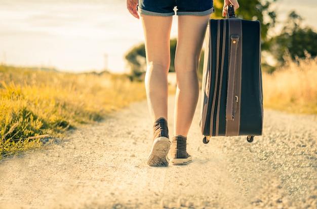 Close-up das pernas de uma mulher em férias andando na estrada segurando a mala em um campo