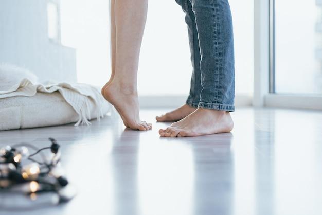 Close-up das pernas descalças do casal se beijando no chão de madeira.