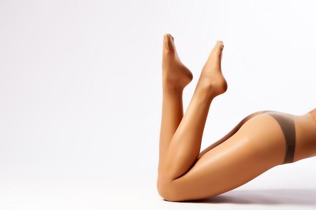 Close-up das pernas finas da mulher bonita posando de meia-calça de nylon cor de carne