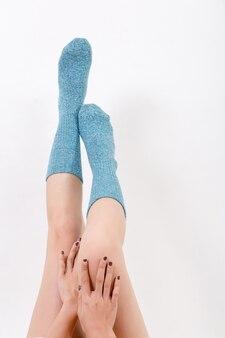 Close up das pernas nuas de uma jovem mulher vestindo meias azuis com os pés. isolado no branco est