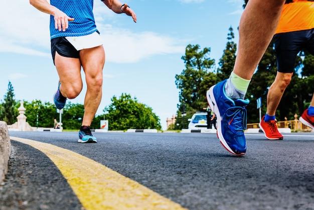 Close-up das pernas poderosas e músculos quádricos de um corredor em pleno esforço em execução