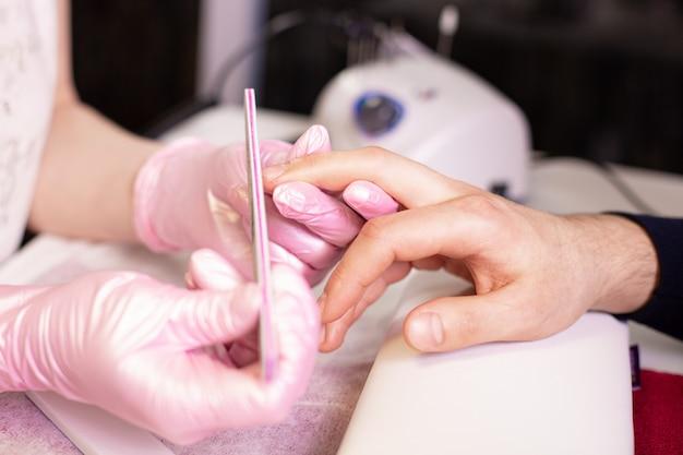 Close-up das unhas de uma pessoa de arquivamento de manicure no salão de beleza