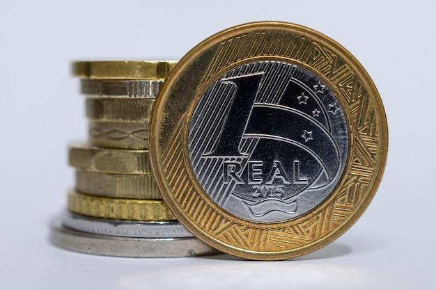 Close up de 1 moeda brasileira real e pilha de várias moedas