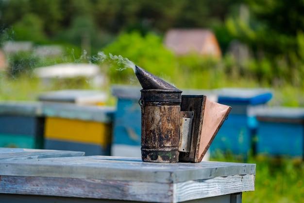 Close up de abelha fumante na colmeia. colmeias em um apiário com abelhas voando para as placas de aterrissagem. apicultura.