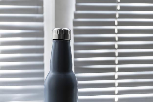 Close-up de aço, garrafa de água térmica reutilizável eco no fundo da janela com venezianas.