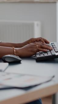 Close-up de adolescente com as mãos no teclado digitando e-mail no computador, trabalhando em um artigo educacional, sentado à mesa