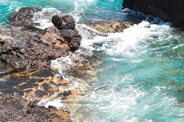 Close-up de água ondulada na costa rochosa