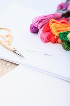 Close up de agulha de bordado, fio dental de cor e tesoura na tela