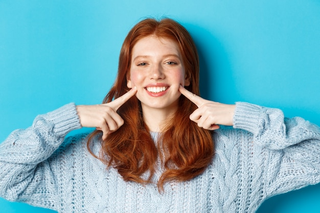 Close-up de alegre adolescente com cabelo ruivo e sardas, cutucando as bochechas, mostrando covinhas e sorrindo com dentes brancos, em pé sobre um fundo azul.