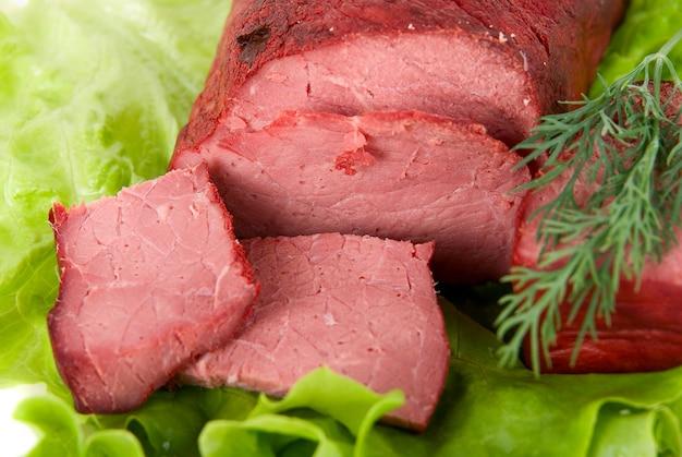 Close up de alface fresca e carne de bovino isolado no branco