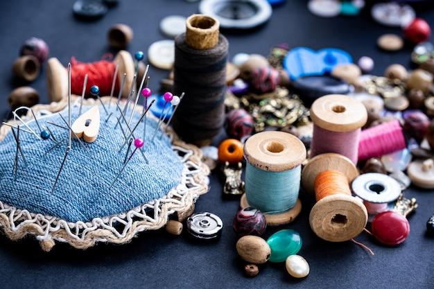 Close up de alfinetes de costura fios retrô e sortimento de grânulos