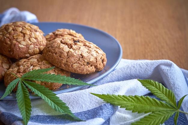 Close-up de algumas cookies de potenciômetro da farinha de aveia em uma placa cinzenta em uma toalha listrada em uma superfície de madeira clara.