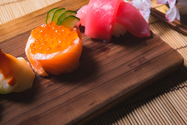 Close-up de alimentos japoneses, conjunto de sushi e bule de chá com sakura na mesa de madeira