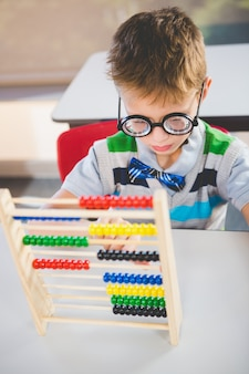 Close-up de aluno contando ábaco na sala de aula