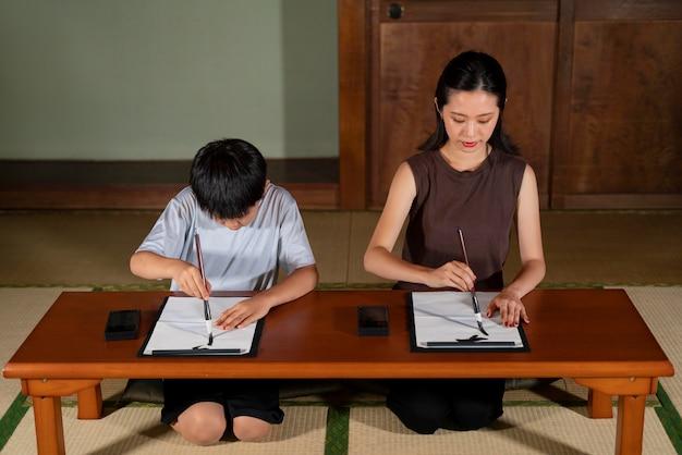 Close-up de alunos fazendo caligrafia japonesa, chamada shodo