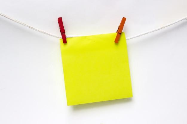 Close-up de amarelo nota em branco pendurado varal contra a parede branca. brincar.