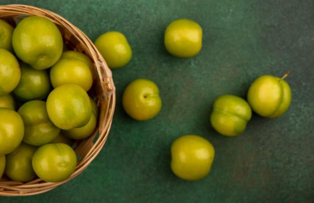 Close-up de ameixas verdes na cesta e sobre fundo verde