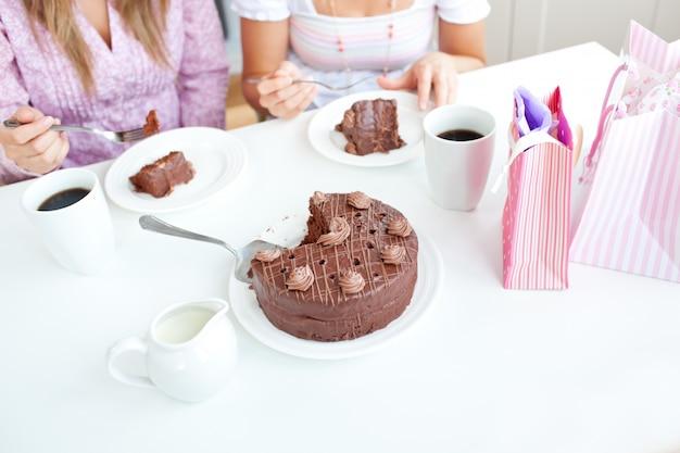 Close-up de amigas caucasianas comendo um bolo de chocolate na cozinha