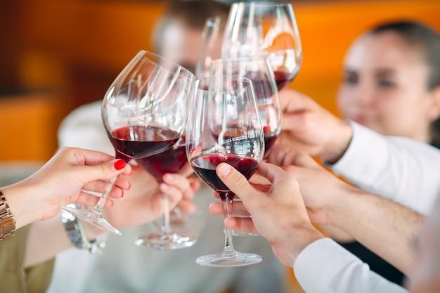 Close-up de amigos brindando copos de vinho na festa