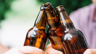 Close-up, de, amigos, clinking, marrom, garrafas cerveja