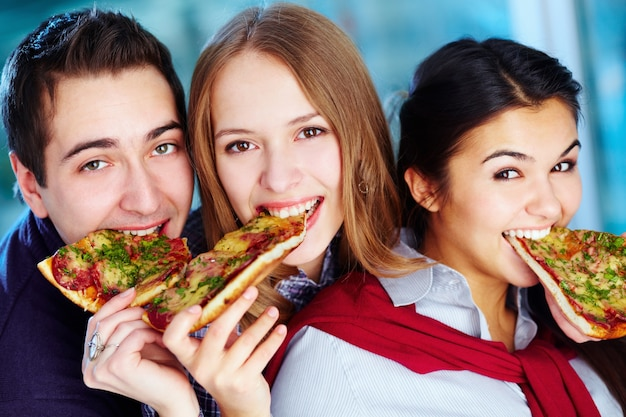 Close-up de amigos comendo uma pizza saborosa