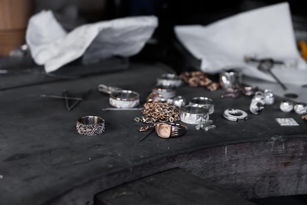 Close-up de anéis inacabados na mesa de ourives