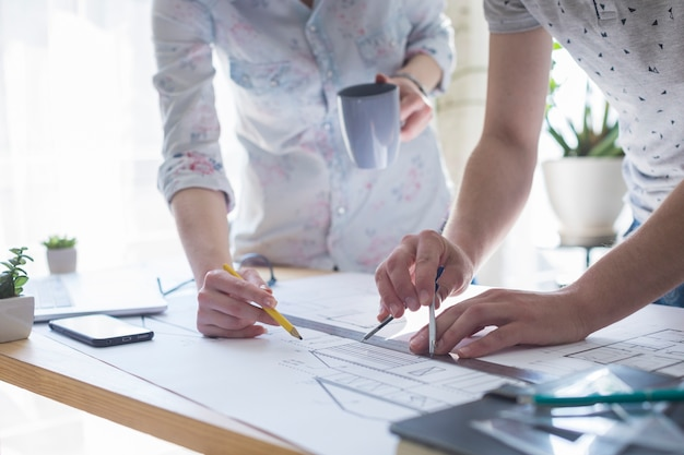 Close-up, de, arquitetura, mãos, trabalhar, ligado, blueprint, sobre, tabela madeira, em, escritório