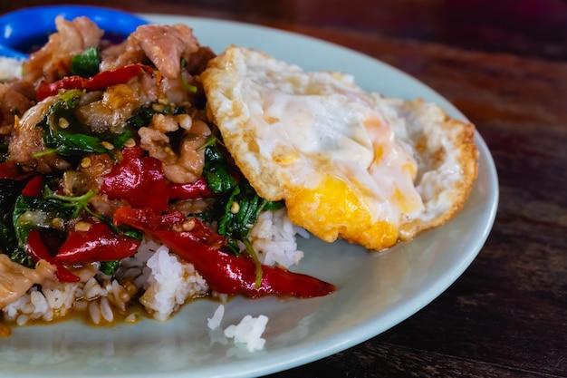 Close-up de arroz coberto com carne de porco frito e manjericão