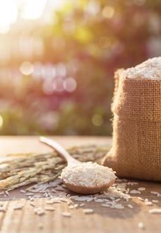 Close-up de arroz de jasmim tailandês na colher e pequeno saco na mesa de madeira