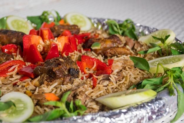 Close up de arroz kebuli com carneiro e tomate como guarnição