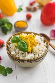 Close-up de arroz saudável; folhas de manjericão e frango na tigela