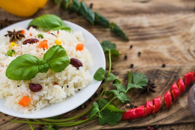 Close-up de arroz saudável; folhas de manjericão; no prato com salsa e pimenta no fundo desfocado