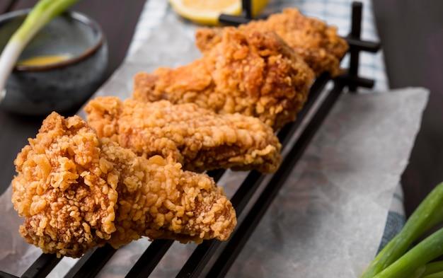 Close-up de asas de frango frito na bandeja com cebolinha
