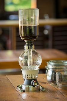 Close-up de aspirador de sifão, xícara de café e sifão aspirador de café na loja