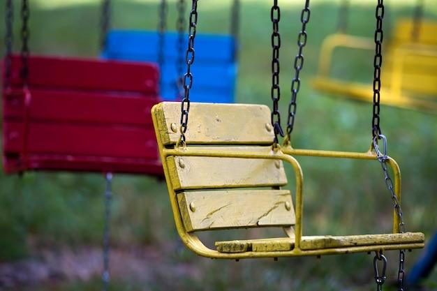 Close-up de assentos vazios de madeira azuis, amarelos, vintage do carrossel multi-colorido pendurado em correntes.