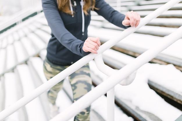 Close-up, de, atleta feminino, exercitar, ligado, escadaria, em, inverno