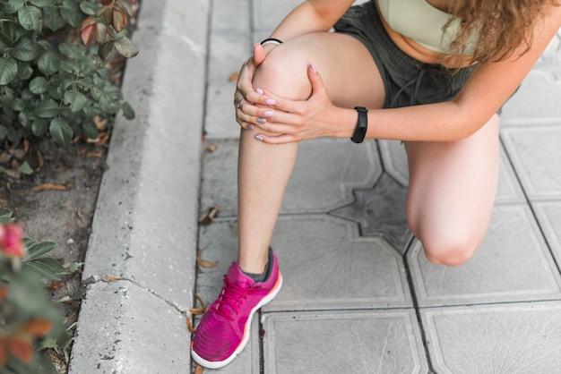 Close-up, de, atleta feminino, tendo, joelho, dor