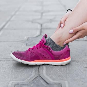 Close-up, de, atleta feminino, tendo, tornozelo, dor, ligado, concreto, pavimento